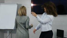 Ungt kvinnligt dansa för affärsfolk som är lyckligt i regeringsställning Lyckligt affärslag som i regeringsställning firar seger  stock video