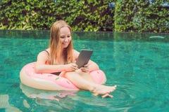 Ungt kvinnligt freelancersammanträde nära pölen med hennes bärbar dator in Royaltyfria Bilder