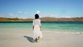 Ungt kvinnligt gå in mot stranden arkivfoto