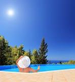 Ungt kvinnligt koppla av i en simbassäng och ett innehav en coctail royaltyfri fotografi
