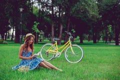 Ungt kvinnligt koppla av på ett grönt gräs med cykeln i en parkera på en solig dag royaltyfri foto