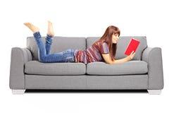Ungt kvinnligt ligga på en soffa och en läsning en bok fotografering för bildbyråer
