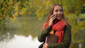 Ungt kvinnligt samtal på mobiltelefonen i höstträdgården nära sjön, härligt skratta för flicka som är offentligt parkerar bakgrun stock video