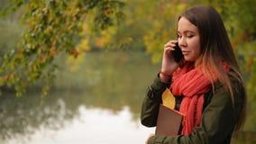 Ungt kvinnligt samtal på mobiltelefonen i höstträdgården nära sjön, härligt skratta för flicka som är offentligt parkerar bakgrun lager videofilmer