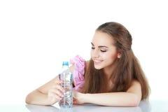 Ungt kvinnligt se på flaskan av vatten, på vit bakgrund Arkivfoto