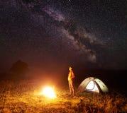 Ungt kvinnligt turist- stående near upplyst tält som campar i berg på natten under stjärnklar himmel royaltyfri foto