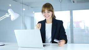 Ungt kvinnligt upphetsat för den lyckade online-transaktionen, betalning vid kreditkorten Arkivfoto