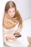 Ungt långhårigt blont sammanträde på en sofa med en gåva boxas Fotografering för Bildbyråer