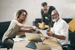 Ungt lag av coworkers som gör stor arbetsdiskussion i modernt kontor Skäggig man som talar med marknadsföringsdirektören och royaltyfria bilder