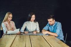 Ungt lag av coworkers som håller ögonen på storyboarden för att skjuta videoen i modernt coworking kontor Teamworkprocess Horison Royaltyfria Bilder
