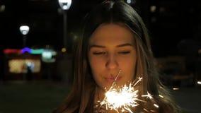 Ungt le hållande tomtebloss för flicka i hennes hand Ståenden av flickainnehavet mousserar i ultrarapid stock video