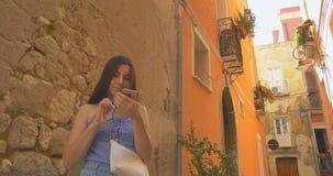 Ungt le kvinnastag i stad på morgonen och användasmartphonen Flickabläddrande internet som smsar med någon lager videofilmer