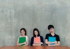 Ungt leende för studentgrupp som kramar skolamappboken arkivfoto