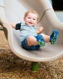 Ungt litet barnpojkebarn som spelar på glidbana fotografering för bildbyråer