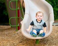 Ungt litet barnpojkebarn som spelar på glidbana Royaltyfri Foto