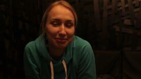 Ungt lyckligt blont kvinnasammanträde i kafét som pratar med vänner som ler att tycka om arkivfilmer