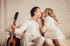 Ungt lyckligt, gift par som kysser sammanträde på soffan royaltyfri bild