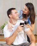 Couple som tycker om exponeringsglas av rött vin på terrass Arkivbilder
