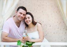 Couple som tycker om exponeringsglas av vitwine på terrass Arkivfoto