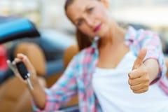 Ungt lyckligt kvinnaanseende nära en cabriolet med tangenterna i H Arkivfoton