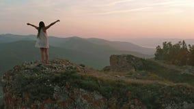 Ungt lyckligt kvinnaanseende på kanten av en klippa Royaltyfri Bild