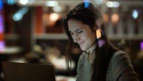 Ungt lyckligt kvinnasammanträde på kafét och använda bärbara datorn Beskåda inom fönstret på kvinnlign som surfar internet