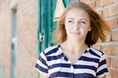 Ungt lyckligt nätt flickaanseende på copyspace för bakgrund för tegelstenvägg Fotografering för Bildbyråer