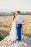 Ungt lyckligt precis gift par som poserar på överkanten av berget Royaltyfria Foton