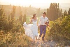 Ungt lyckligt precis gift par som poserar på överkanten av berget Royaltyfri Fotografi
