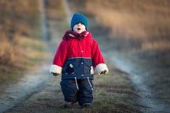 Ungt lyckligt spela för pojke som är utomhus- på landsvägen Royaltyfri Foto