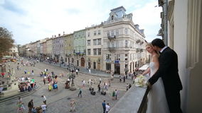 Ungt lyxigt ursnyggt lyckligt brud- och brudgumanseende på balkongen Bakgrund av den soliga forntida Lviv staden lager videofilmer