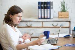 Ungt mammaarbete- och innehavbarn i kontoret arkivfoton