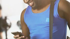 Ungt manligt anseende i idrottshall med påsen på skuldran, läs- meddelande på mobiltelefonen arkivfilmer
