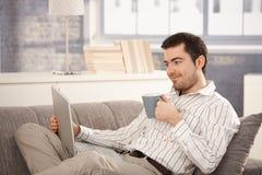 Ungt manligt bläddra internetsammanträde på soffan royaltyfri fotografi