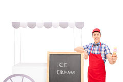 Ungt manligt försäljareanseende vid en glassställning Arkivfoton
