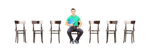 Ungt manligt sammanträde på en stol och en väntande på jobbintervju Royaltyfri Bild