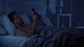 Ungt manligt smsa på smartphonen och le och att prata med flickvännen, grej arkivfilmer