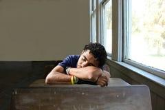 Ungt manligt sova på ett skrivbord i ett klassrum royaltyfria bilder