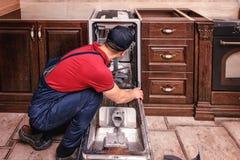Ungt manligt teknikerRepairing Dishwasher In kök royaltyfria bilder