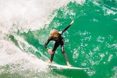Ungt manligt tonårigt surfa en stor våg Fotografering för Bildbyråer