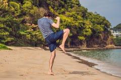 Ungt manligt utarbeta på stranden, sportig man som gör övningar arkivfoto