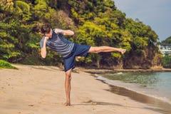 Ungt manligt utarbeta på stranden, sportig man som gör övningar arkivbild