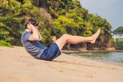 Ungt manligt utarbeta på stranden, sportig man som gör övningar royaltyfri fotografi