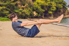 Ungt manligt utarbeta på stranden, sportig man som gör övningar royaltyfri foto