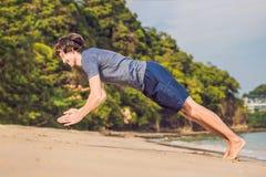 Ungt manligt utarbeta på stranden, sportig man som gör övningar royaltyfri bild