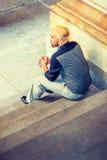 Ungt mansammanträde för latinamerikansk amerikan på trappa Arkivfoto
