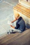 Ungt mansammanträde för latinamerikansk amerikan på trappa, läsebok Royaltyfria Foton