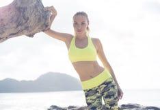 Ungt nätt blont kvinnligt bärande övningsklädanseende på den tropiska stranden nära havet Royaltyfria Bilder