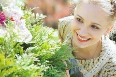 Ungt nätt kvinnanederlag bak en grön buske Fotografering för Bildbyråer