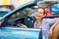 Ungt nätt kvinnasammanträde i en konvertibel bil med tangenterna in Fotografering för Bildbyråer
